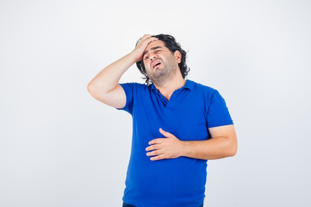 Oudere man die lijdt aan sterke hoofdpijn in blauw t-shirt en op zoek geïrriteerd, vooraanzicht.