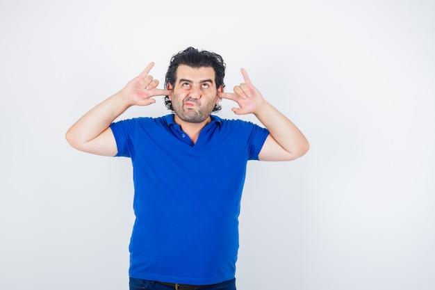 Oudere man die oren met vingers inplugt, lippen in blauw t-shirt buigt en peinzend kijkt. vooraanzicht.
