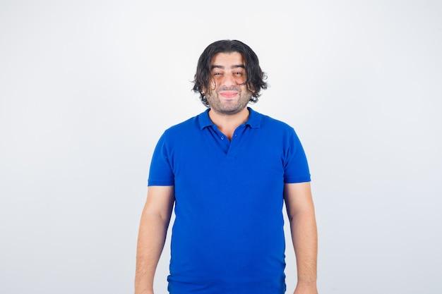 Oudere man die rechtop staat, grimassen in blauw t-shirt, spijkerbroek en op zoek gelukkig, vooraanzicht.
