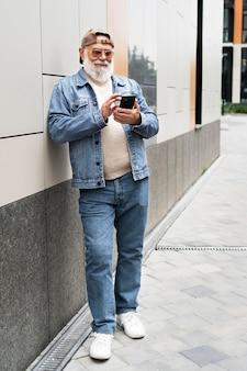 Oudere man die smartphone buiten in de stad gebruikt