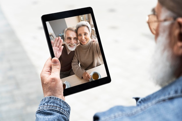 Oudere man die tablet buiten in de stad gebruikt voor videogesprekken
