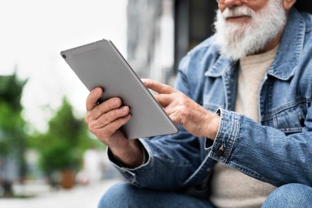 Oudere man die tablet buiten in de stad gebruikt