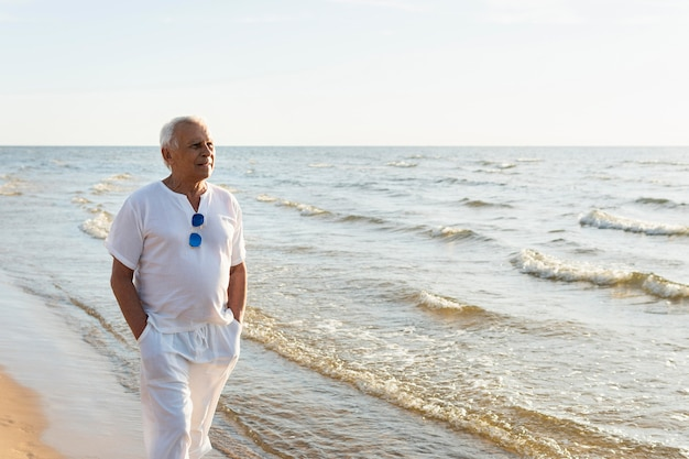 Oudere man die van het uitzicht geniet tijdens het wandelen op het strand