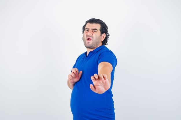 Oudere man die zich rechtop bevindt terwijl hij in blauw t-shirt, spijkerbroek staat en boos kijkt. vooraanzicht.