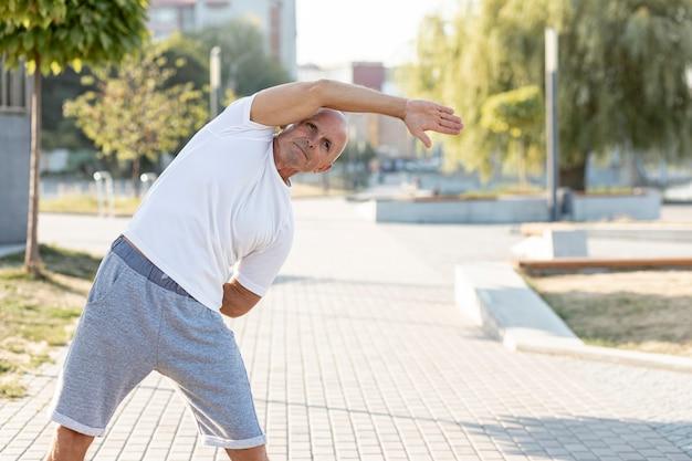 Oudere man die zich uitstrekt over een trottoir