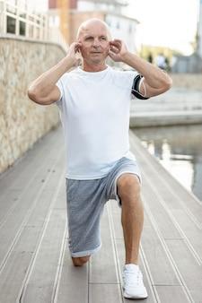 Oudere man doet oefeningen naast water