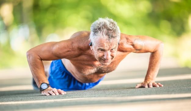 Oudere man doet push-ups op de weg in de natuur tijdens een zonnige zomerdag.