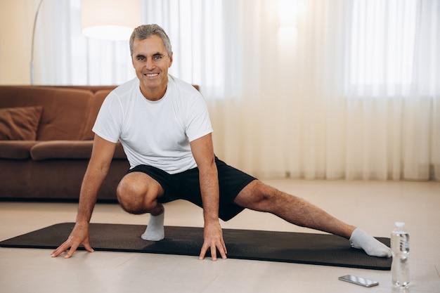 Oudere man doet side lunge oefening