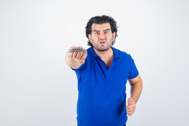 Oudere man dreigt met ketting omwikkeld door vuist in blauw t-shirt en op zoek agressief. vooraanzicht.