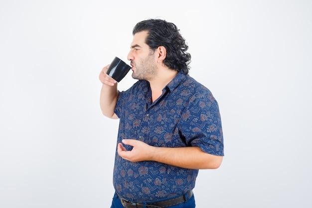 Oudere man drinkt terwijl hij wegkijkt in shirt en verheugd kijkt, vooraanzicht.