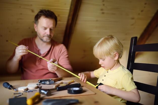 Oudere man en kleine jongen maken samen een houten speelgoed.