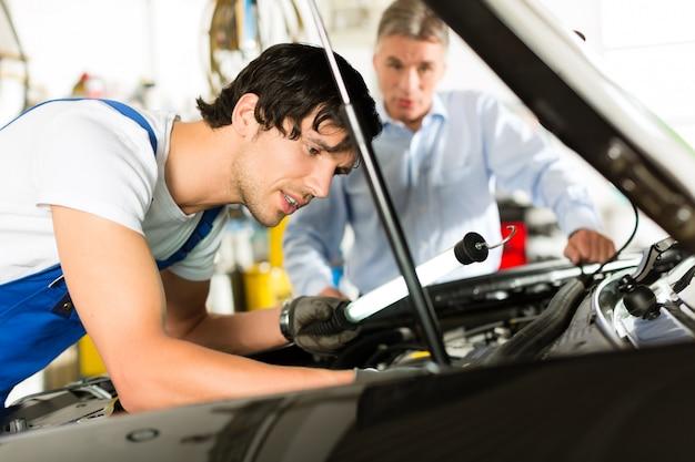 Oudere man en monteur kijken naar motor van een auto