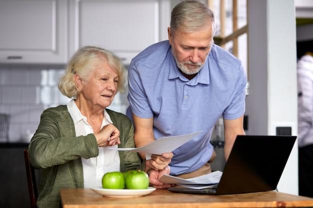 Oudere man en vrouw beheren maandelijks gezinsbudget samen, gericht getrouwd stel met behulp van computerbankieren, rekeningen tellen in de keuken