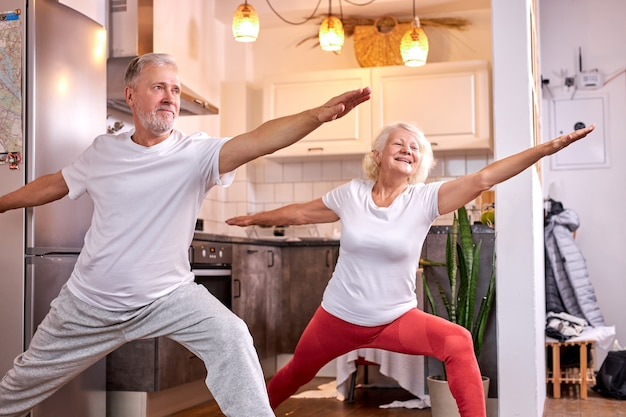 Oudere man en vrouw beoefenen van virabhadrasana vormen thuis, yoga. gezonde levensstijl concept