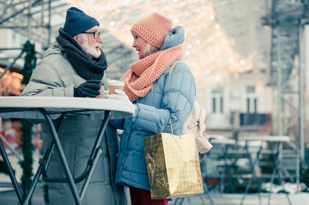 Oudere man en vrouw in warme winterkleren staan tegenover elkaar aan de buitentafel en hebben een gesprek