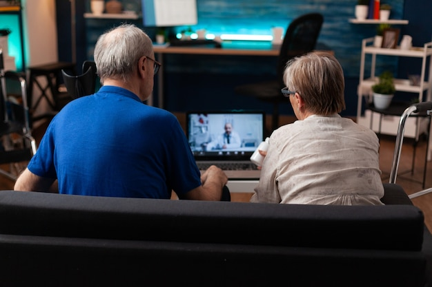 Oudere man en vrouw praten online met dokter
