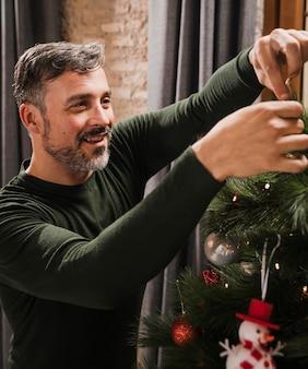 Oudere man genieten van kerstboom decoratie
