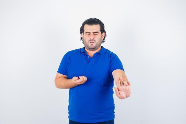 Oudere man hand uitrekken als iets in blauw t-shirt vasthouden en kalm kijken