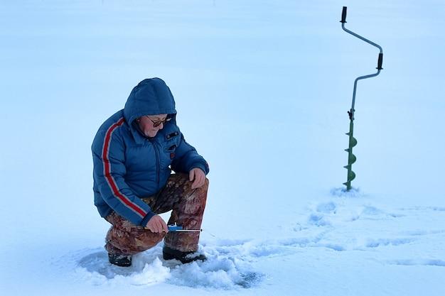 Oudere man heeft in de winter op het meer gevist