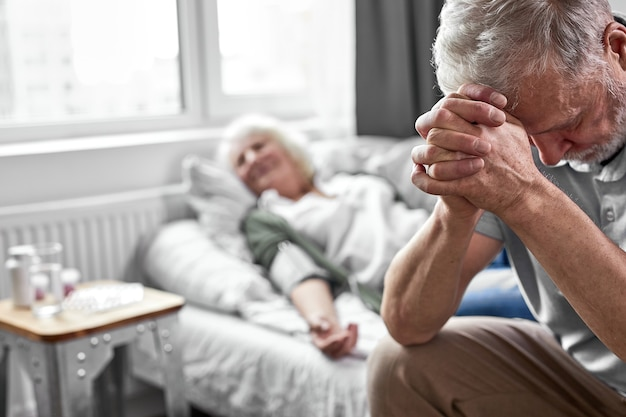 Oudere man huilend en rouwend om het verlies van zijn vrouw, zittend aan haar zijde. focus op boos man naar beneden te kijken. coronavirus, covid-19 concept