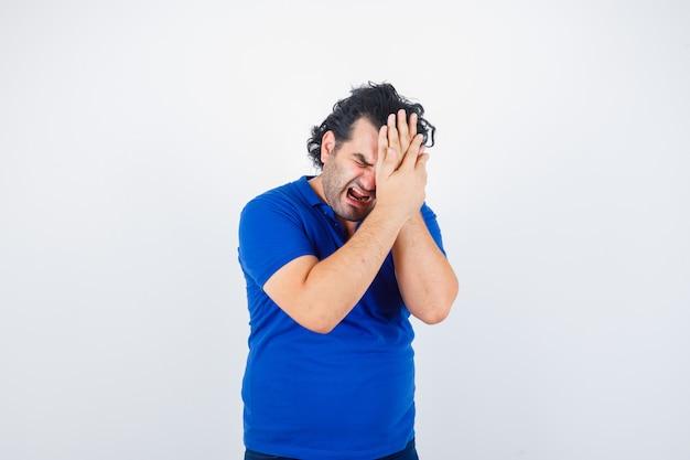 Oudere man in blauw t-shirt die aan migraine lijdt en geïrriteerd, vooraanzicht kijkt.