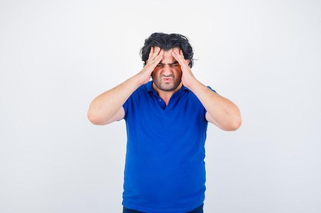 Oudere man in blauw t-shirt hoofdpijn lijden en op zoek geërgerd, vooraanzicht.