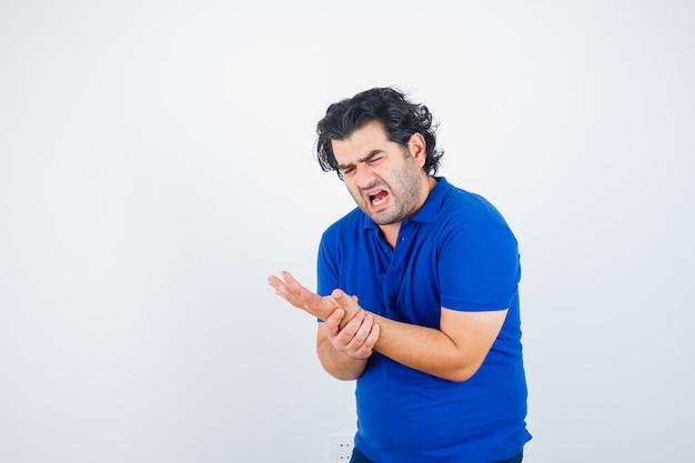 Oudere man in blauw t-shirt houdt zijn pijnlijke pols vast en kijkt bedroefd, vooraanzicht.