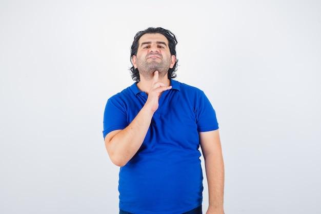 Oudere man in blauw t-shirt met zelfmoordgebaar en peinzend, vooraanzicht op zoek.