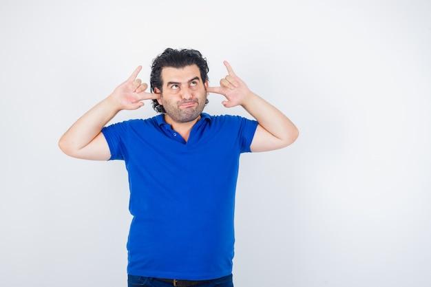 Oudere man in blauw t-shirt oren met vingers inpluggen, lippen gebogen en peinzend, vooraanzicht op zoek.