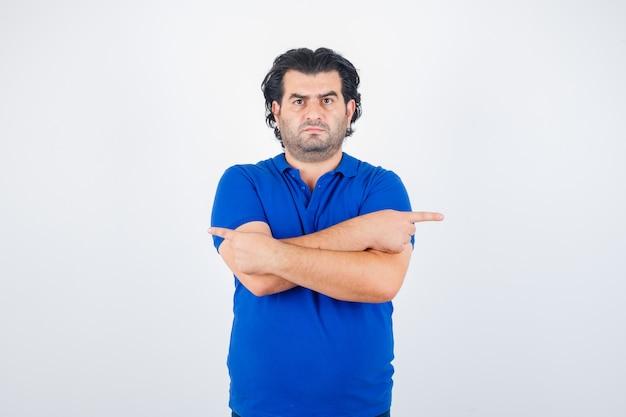 Oudere man in blauw t-shirt, spijkerbroek met twee armen gekruist, tegengestelde richtingen wijzend met wijsvingers en boos, vooraanzicht op zoek.
