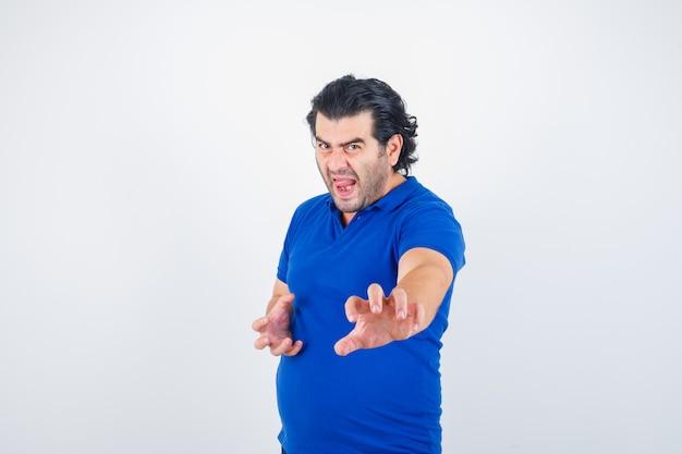 Oudere man in blauw t-shirt, staande in strijd pose en kijkt boos, vooraanzicht.