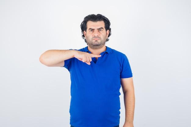 Oudere man in blauw t-shirt, wijst naar rechts met wijsvinger en kijkt boos, vooraanzicht.