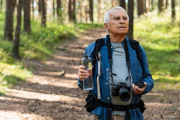 Oudere man in de natuur met camera en waterfles