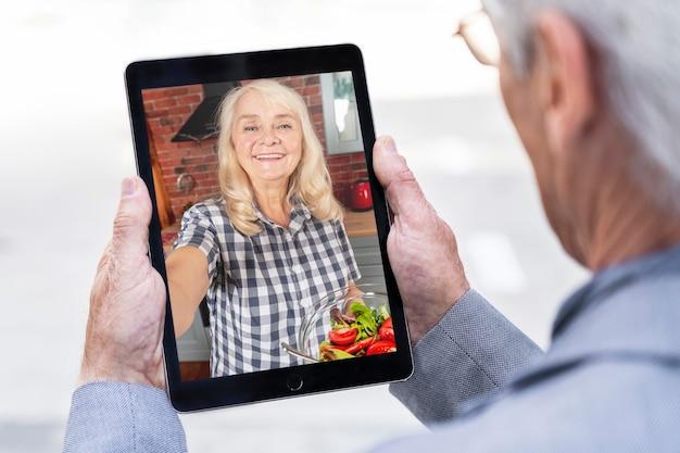 Oudere man in de stad die tablet gebruikt voor videogesprek