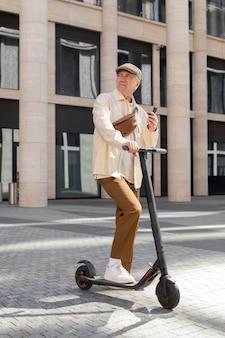 Oudere man in de stad met een elektrische scooter met smartphone