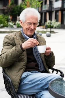 Oudere man in de stad met een kopje koffie