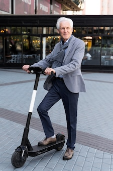 Oudere man in de stad met elektrische scooter
