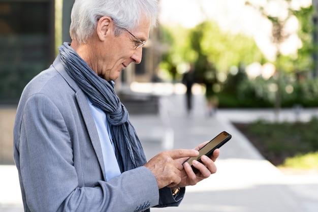Oudere man in de stad met smartphone