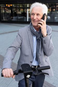 Oudere man in de stad praten op smartphone