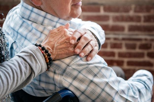 Oudere man in een rolstoel die de hand van zijn vrouw op zijn schouder houdt