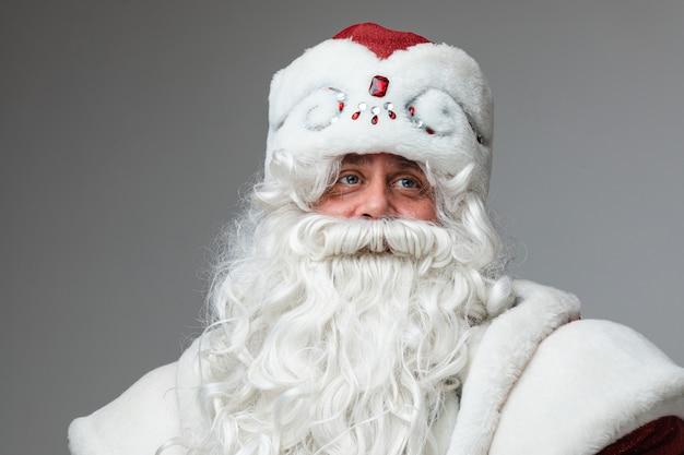 Oudere man in kerstmuts met grijze baard en snor