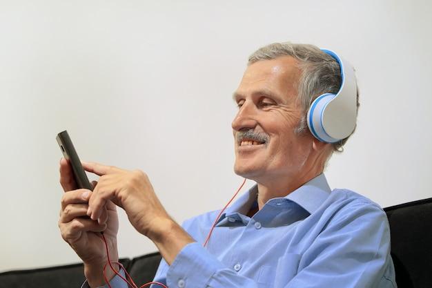 Oudere man in koptelefoon luisteren naar muziek