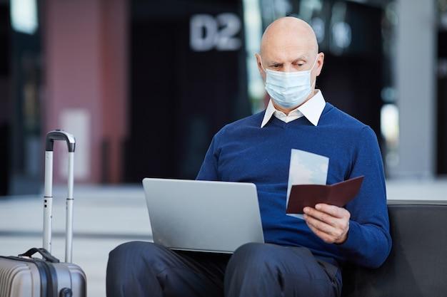 Oudere man in masker met behulp van laptop die hij de kaartjes op de luchthaven uitwisselt