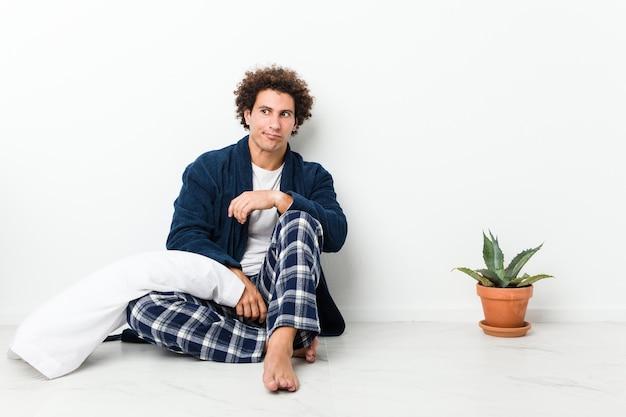 Oudere man in pyjama zittend op de vloer van het huis, verward, twijfelachtig en onzeker.
