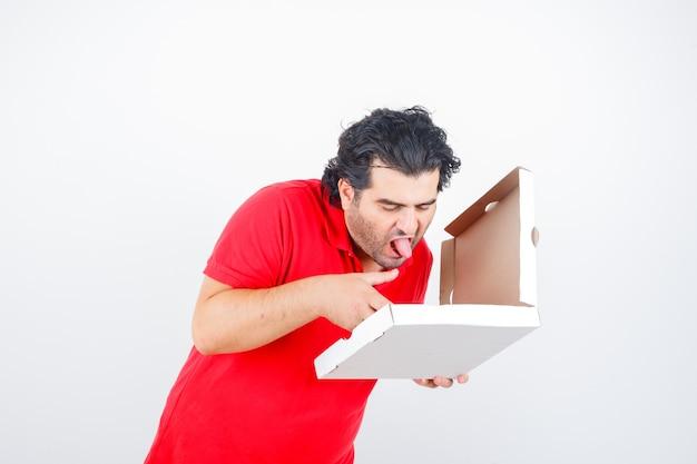 Oudere man in rood t-shirt kijken naar geopende pizzadoos terwijl tong uitsteekt en hongerig, vooraanzicht kijkt.