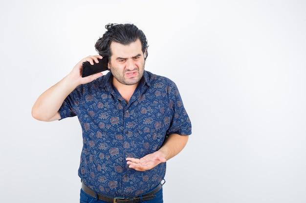 Oudere man in shirt praten op mobiele telefoon en op zoek boos, vooraanzicht.