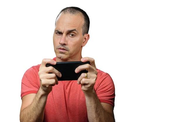 Oudere man in vrijetijdskleding, verdacht en smartphone horizontaal te houden.