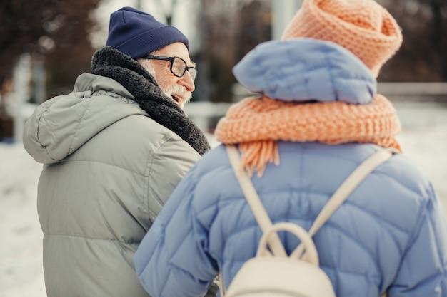 Oudere man in winterjas en hoed die naar zijn vrouw glimlacht terwijl hij op winterdag met haar loopt