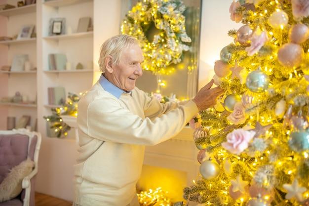 Oudere man kerstboom samen versieren