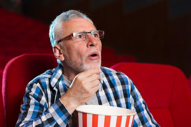 Oudere man kijkt naar film in de bioscoop